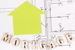 Inscription mortgage with home shape on construction housing plan, buying house concept. Inscription mortgage with home shape on construction diagrams of housing stock image