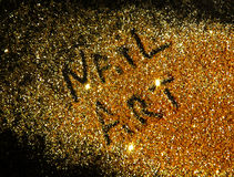 Inscription Nail Art on golden glitter sparkle on black background Royalty Free Stock Photography