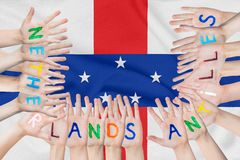 Inscription Netherlands Antilles on the children`s hands against the background of a waving flag of the Netherlands Antilles stock photos