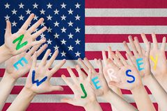 Inscription New Jersey on the children`s hands against the background of a waving flag of the USA.  royalty free stock photos
