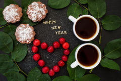 Inscription of new year on a black board with cupcake and heart in the form cherries Stock Photos