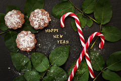 Inscription of new year on a black board with cupcakes and candy red Stock Images