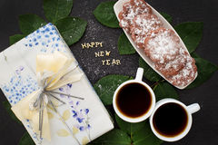 Inscription of new year on a black board with  gift, muffins and coffee Stock Images