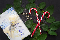 Inscription of new year on a black board with gift and red candy Royalty Free Stock Photos