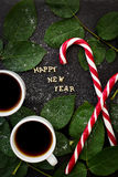 Inscription of new year on a black board with sprigs  leaves and red candy Royalty Free Stock Image