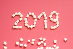 Inscription new year 2019 of white marshmallow on a pink background royalty free stock image