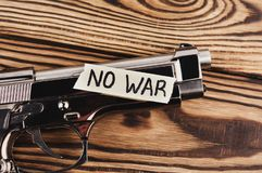 Inscription NO WAR on torn paper and glossy pistol. On old rustic wooden weathered planks stock image