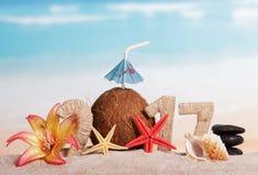 Inscription 2017, noix de coco, étoile de mer, coquille, fleur en sable contre la mer Photographie stock