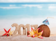 Inscription 2017, noix de coco, étoiles de mer et fleur en sable contre la mer Images stock