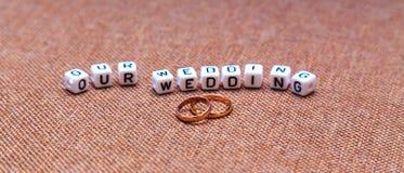 Inscription notre mariage et anneaux de mariage sur le textur brun de tissu Image stock