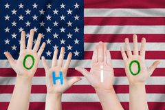 Inscription Ohio on the children`s hands against the background of a waving flag of the USA.  royalty free stock images