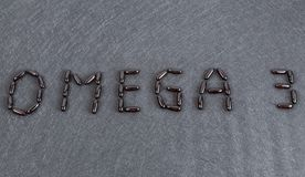 Inscription Omega 3 on black background Gel capsules stock image