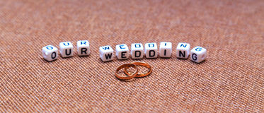 Inscription Our wedding and wedding rings on brown fabric textur Stock Image