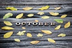 inscription outubro, letras de madeira Quadro das folhas amarelas, fundo de madeira foto de stock