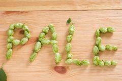 The inscription pale with hop cones on wooden background. Ingredient in beer industry. Craft beer brewing. For ale or lager royalty free stock photography