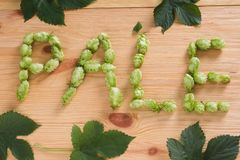 The inscription pale with hop cones on wooden background with le. Aves. Ingredient in beer industry. Craft beer brewing. For ale or lager stock photo