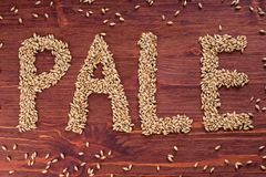 The inscription of pale by malt grains on wood background. Craft. Beer brewing from grain barley malt. Ale or lager from pale or dark pilsner malt stock photos