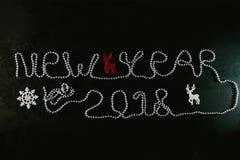 Inscription par nouvelle année sur un fond noir Photographie stock
