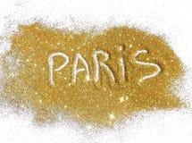 Inscription Paris on golden glitter sparkles on white background Stock Photography