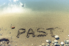 The inscription PAST on a wet sand seacoast. Toned Royalty Free Stock Image
