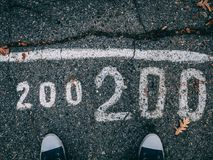 Asphalt legs and inscription. 200 inscription on the pavement in autumn. Top view stock images