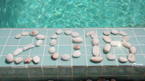 Inscription 2018 of pebble on a pool side stock video