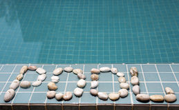 The inscription pool is laid out by pebble on a pool side Royalty Free Stock Image