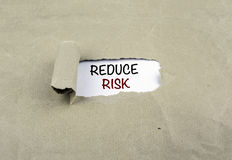 Inscription revealed on old paper - REDUCE RISK Royalty Free Stock Images