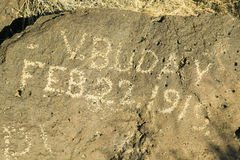 Inscription on rock at Petroglyph National Monument reads, February 22, 1919 demonstrating vandalism of Native American petroglyph Royalty Free Stock Photography