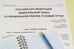 The inscription in Russian `Russian Federation. Federal law on special assessment of working conditions`. The study of law. Notepad and pen stock photography