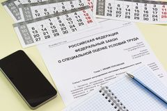 The inscription in Russian `Russian Federation. Federal law on special assessment of working conditions`. The study of law. Notebo. Ok, pen and smartphone on the stock photos