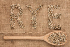 Inscription rye with a wooden spoon on burlap Stock Photos