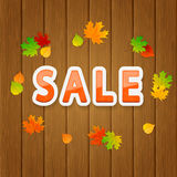 Inscription Sale and autumn leaves on wooden background Royalty Free Stock Image