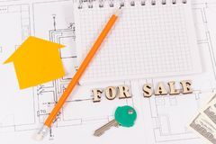 Inscription for sale, key, notepad and money on electrical diagrams, selling and buying house or flat concept