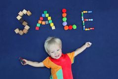 Inscription SALE made from different toys and cute smiling blond. Boy on blue textile background. Good for baby store royalty free stock photography