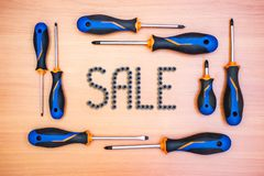 Inscription sale from screws in a frame from different screwdrivers on a wooden background royalty free stock photos