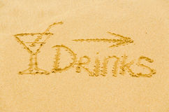 Inscription on the sand. Word  drinks  on the yellow sand of the sea Stock Photo
