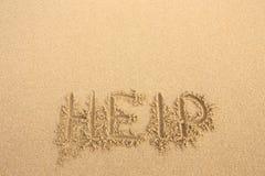The inscription on the sand beach. Help Stock Image