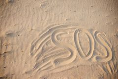 The inscription on the sand beach SOS.  stock photography