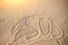 The inscription on the sand beach SOS.  royalty free stock photo