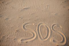 The inscription on the sand beach SOS.  royalty free stock photos