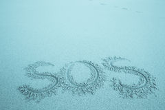 The inscription on the sand beach. SOS. With space for text Royalty Free Stock Image