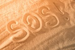 Inscription on the sand beach SOS. With space for text. Inscription on the sand beach SOS. With copy space for text Royalty Free Stock Images