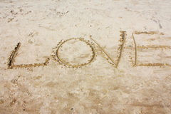 The inscription on the sand. Beautiful inscription love on a clean white sand stock photo