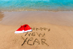 Inscription on the sand and cap of Santa Claus Stock Images