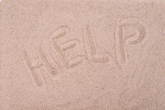 The inscription on the sand Help, close-up. The inscription on the sand Help,  close-up Stock Photo