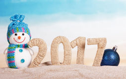 Inscription 2017 in the sand, snowman, Christmas ball Royalty Free Stock Images