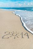 Inscription 2014 on sea sand beach with the sun rays Stock Image