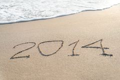 Inscription 2014 on sea sand beach with the sun rays Royalty Free Stock Image