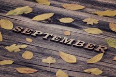 Inscription September on a wooden background, frame of yellow le. Aves Royalty Free Stock Image